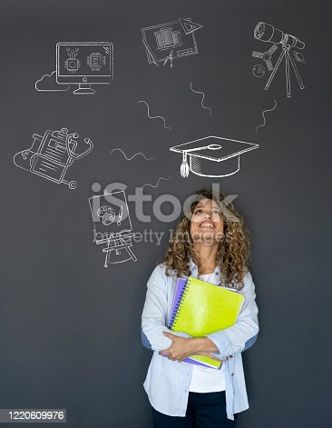 Happy student thinking about what to study as her major and looking at the options on a blackboard while smiling