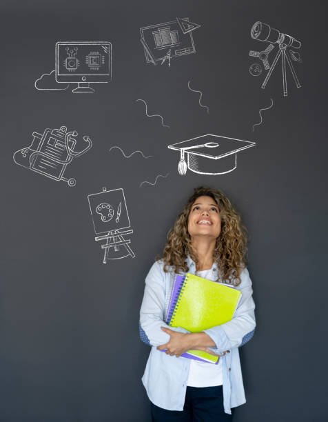 Happy student thinking about what to study Happy student thinking about what to study as her major and looking at the options on a blackboard while smiling major military rank stock pictures, royalty-free photos & images
