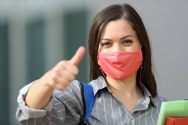 Happy student wearing mask with thumbs up stock photo