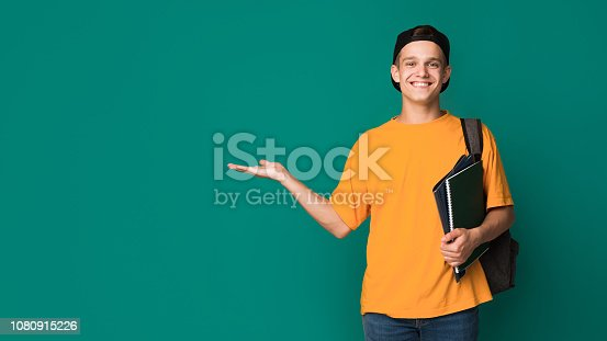 istock Happy student with books holding something on palm 1080915226
