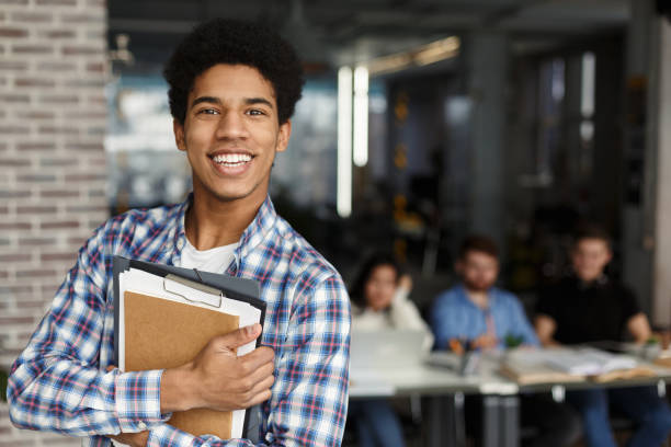 도서관에서 카메라를 보고 책을 가진 행복한 학생 - 십대 소년 뉴스 사진 이미지