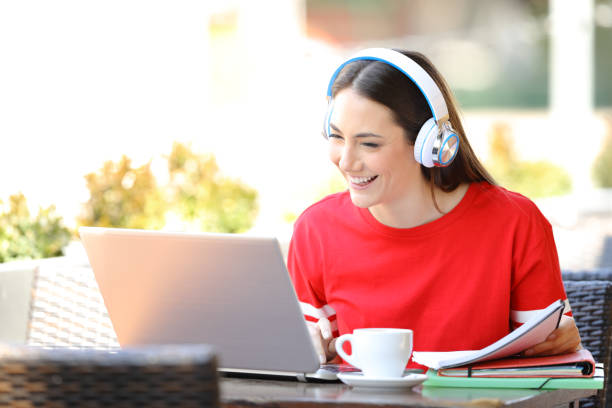 Happy student with headphones e-learning with a laptop stock photo
