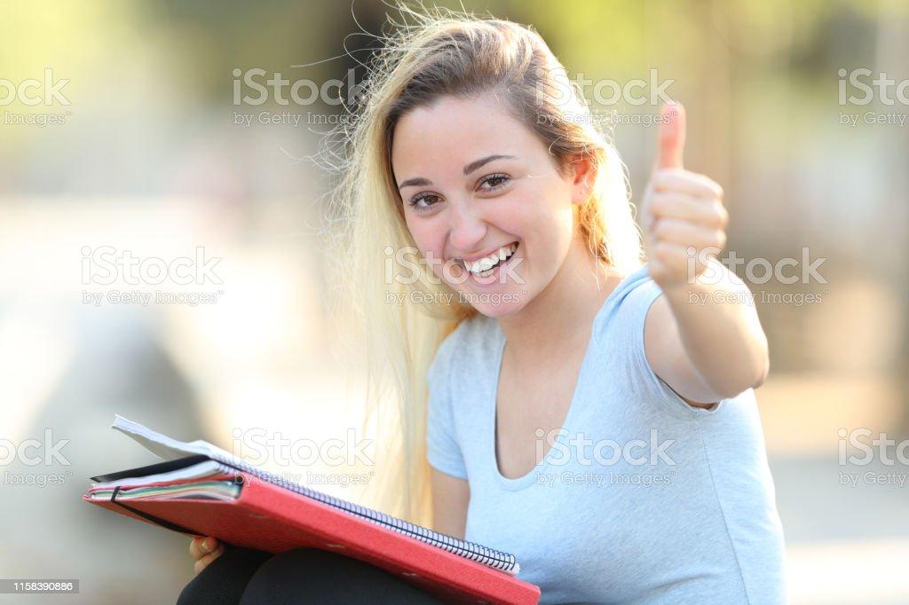 L'étudiant heureux avec des pouces vers le haut regarde l'appareil-photo - Photo de Accord - Concepts libre de droits