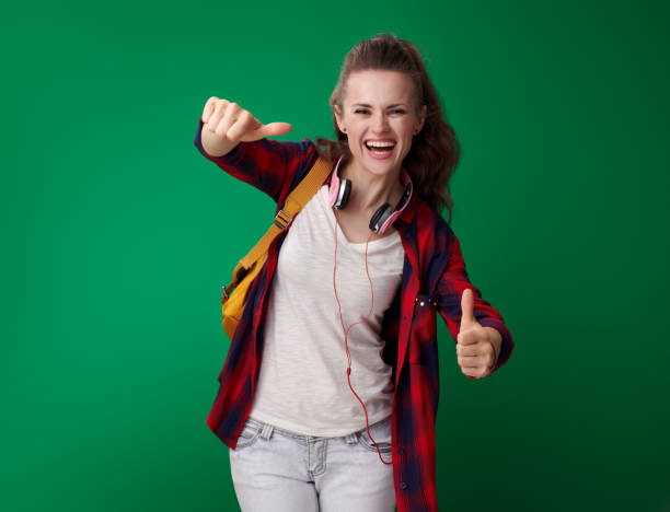 happy student woman showing thumbs up on green background - ragazza auricolari rossi foto e immagini stock