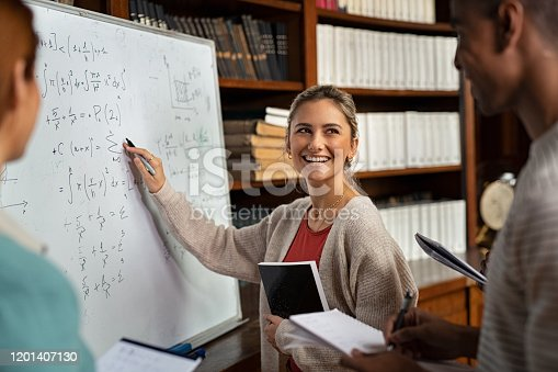 Happy girl writing math formulas on whiteboard while looking her classmate. Young woman solving arithmetic problem while standing with university students in classroom. Smiling college student holding book explaining math problem at school.