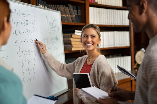 Happy student writing exercise on whiteboard Happy girl writing math formulas on whiteboard while looking her classmate. Young woman solving arithmetic problem while standing with university students in classroom. Smiling college student holding book explaining math problem at school. mathematical symbol stock pictures, royalty-free photos & images