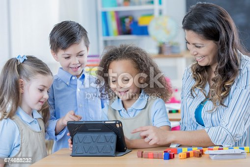 istock Happy students and teacher use digital tablet in class 674688232