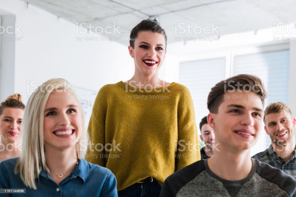 Happy students attending mental therapy session Happy young university students attending mental health therapy session. Smiling woman is looking away while standing by friends. They are attending meeting in lecture hall. 18-19 Years Stock Photo