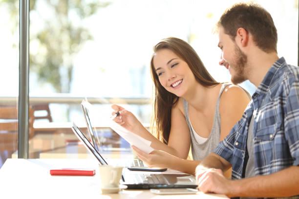 estudiantes felices revisando el documento en una cafetería - happy couple sharing a cup of coffee fotografías e imágenes de stock
