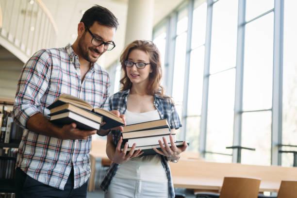 Glückliche Schüler paar in der Schulbibliothek haben Diskussion – Foto