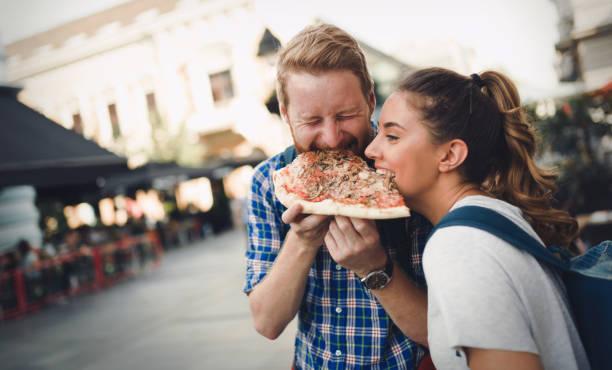 estudiantes felices comiendo pizza en la calle - couple lunch outdoors fotografías e imágenes de stock