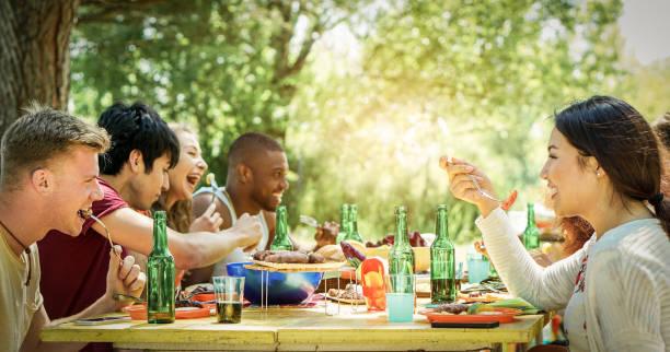 glückliche schüler grillfest am sommertag im garten hausgarten - warme junge fröhliche menschen essen lecker bbq-abendessen - konzept über positive stimmung mit freunden - fokus auf rechts blonder mann - filter - partysalate stock-fotos und bilder