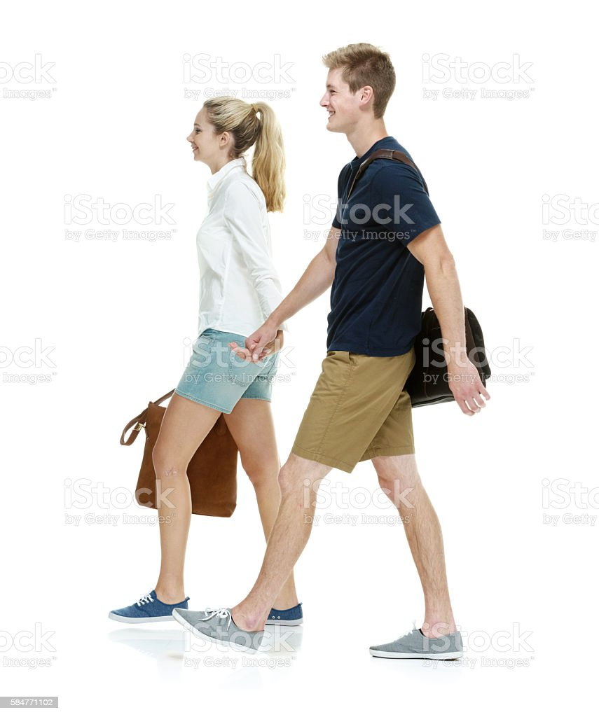 Happy students holding hands and walking stock photo