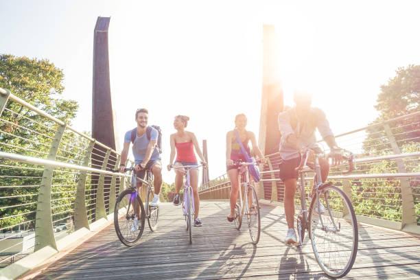glückliche schüler auf vintage fahrräder fahren im stadtpark - jungen freunden gemeinsam spaß haben - jugend, freundschaft und sport konzept - schwerpunkt richtigen mann - warme filter mit original sonnenlicht zurück - städtetrip stock-fotos und bilder