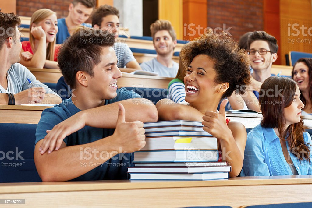 Happy students Group of cheerful students sitting in the lecture hall. Focus on the cute young couple laughing with thumps up. 20-24 Years Stock Photo