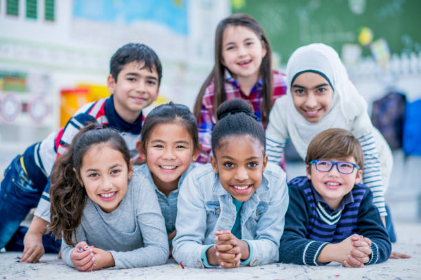 Happy Students A diverse group of elementary school students are indoors in their classroom. They are lying on the floor and on each other. Everyone is smiling at the camera. immigrant stock pictures, royalty-free photos & images