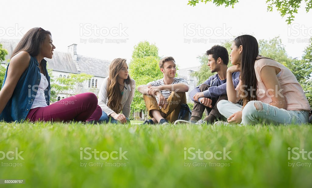 Happy students sitting outside on campus stock photo