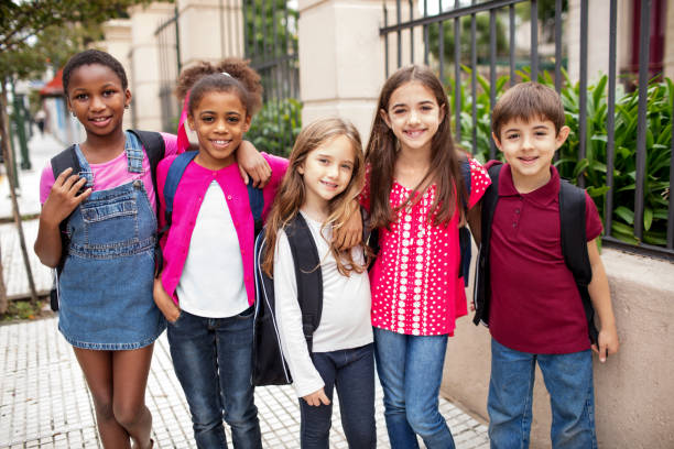 Happy students standing arm around outside school stock photo