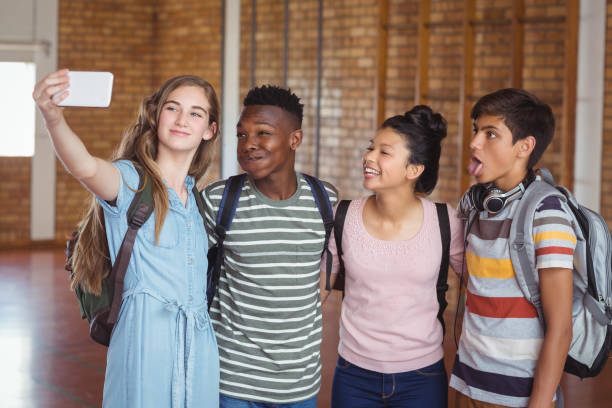 Happy students taking selfie on mobile phone in campus stock photo