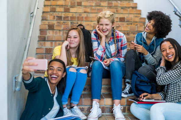 Happy students taking selfie on steps in school Happy female students taking selfie while sitting on steps. Teenage friends are posing while looking at smart phone. Girls are wearing casuals in school. teenagers only stock pictures, royalty-free photos & images