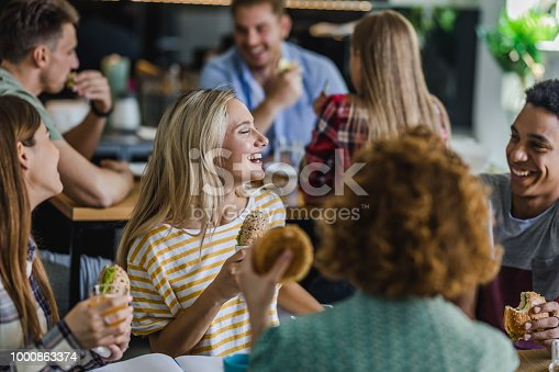 Large group of university students communicating while eating sandwiches on a lunch break at cafeteria. Focus is on blond woman.