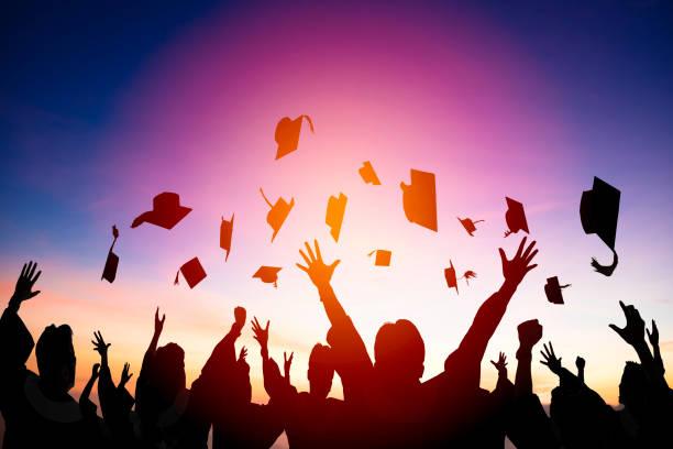estudiantes felices lanzando gorras de graduación en el air - graduación fotografías e imágenes de stock