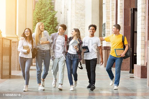 Diverse students walking together in campus, having break after classes