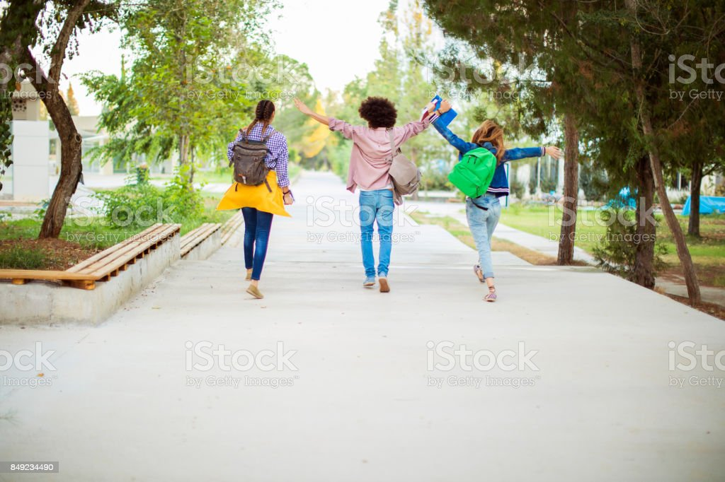 Happy students with arms raised on air stock photo