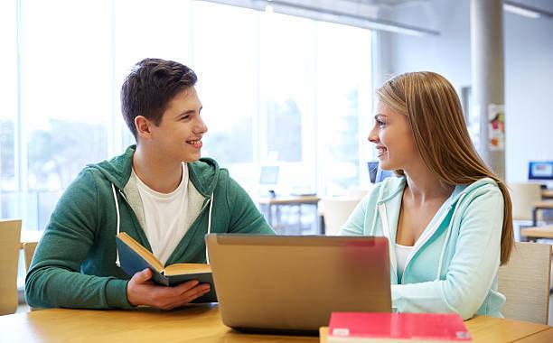 studenti felici con un computer portatile e libri in biblioteca - compagni scuola foto e immagini stock
