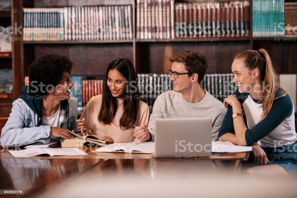 Happy students working on college project in library stock photo