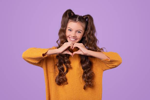 Happy stylish child gesturing heart stock photo