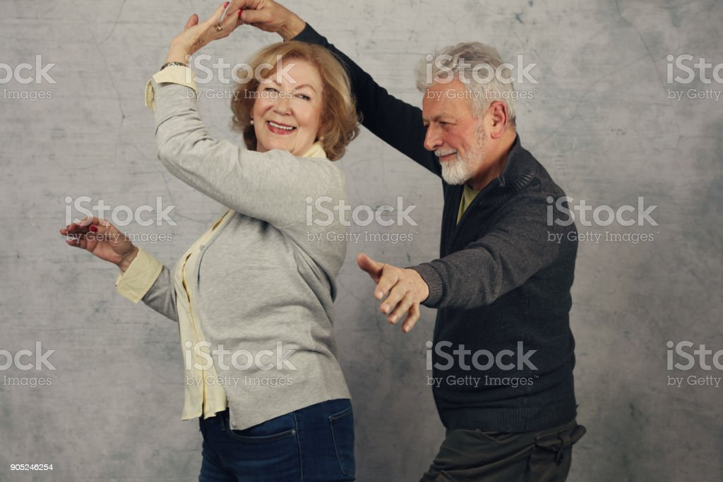 Happy stylish elderly couple dancing and laughing. Vintage image stock photo
