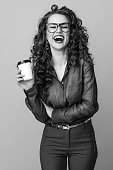 happy stylish woman with long wavy brunette hair with a coffee cup on background