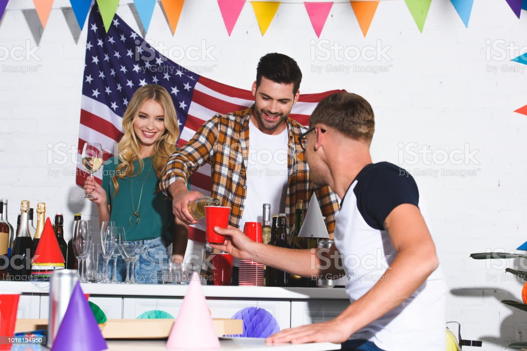 happy stylish young friends drinking wine and partying at home stock photo