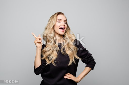 Happy stylist woman pointing at copy space. Gorgeous blond female is wearing street outfit. She is standing over white background.