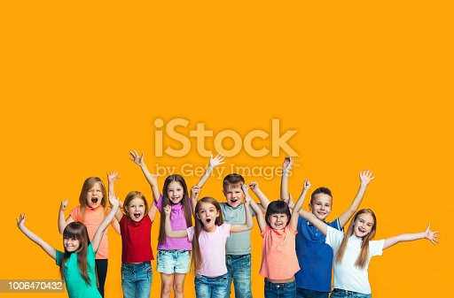 We won. Winning success happy teen girls and boys celebrating being a winner. Dynamic image of caucasian Children on orange studio background. Victory, delight concept. Human facial emotions concept. Trendy colors