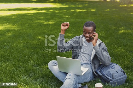 istock Happy successful african-american student with arm raised in the air 917659944