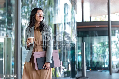 Outdoor shot of a smiling Asian businesswoman holding coffee and files on the street.