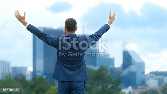 istock Happy Successful Business Man Raises His Hands, He Has His Business Victory. In The Background Big City with Skyscrapers. 867704450