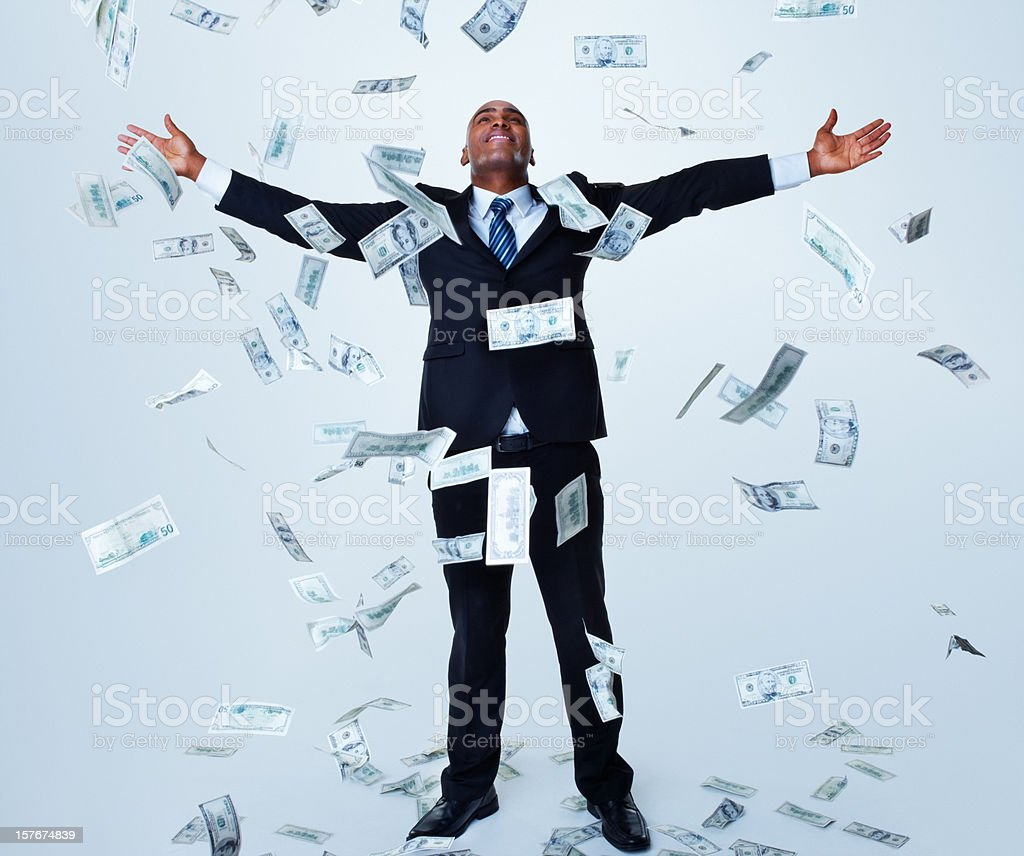 Happy successful business man under money rain against white stock photo