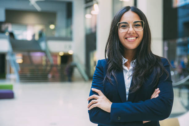 Happy successful businesswoman posing in office hall stock photo
