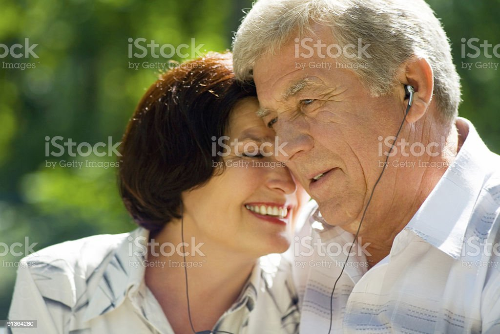 Happy successful elderly couple listening music in headset together, outdoors royalty-free stock photo