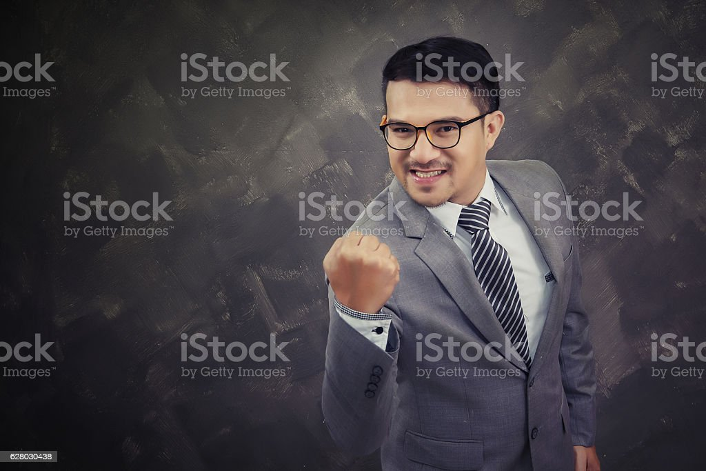 Happy successful gesturing businessman, isolated over brick background stock photo