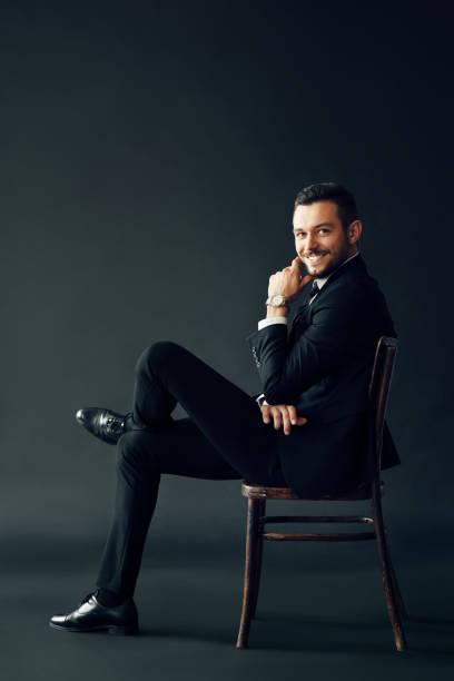 Glücklicher erfolgreicher Mann im schwarzen Anzug lächelnd und mit Blick auf die Kamera sitzend auf dem Stuhl – Foto