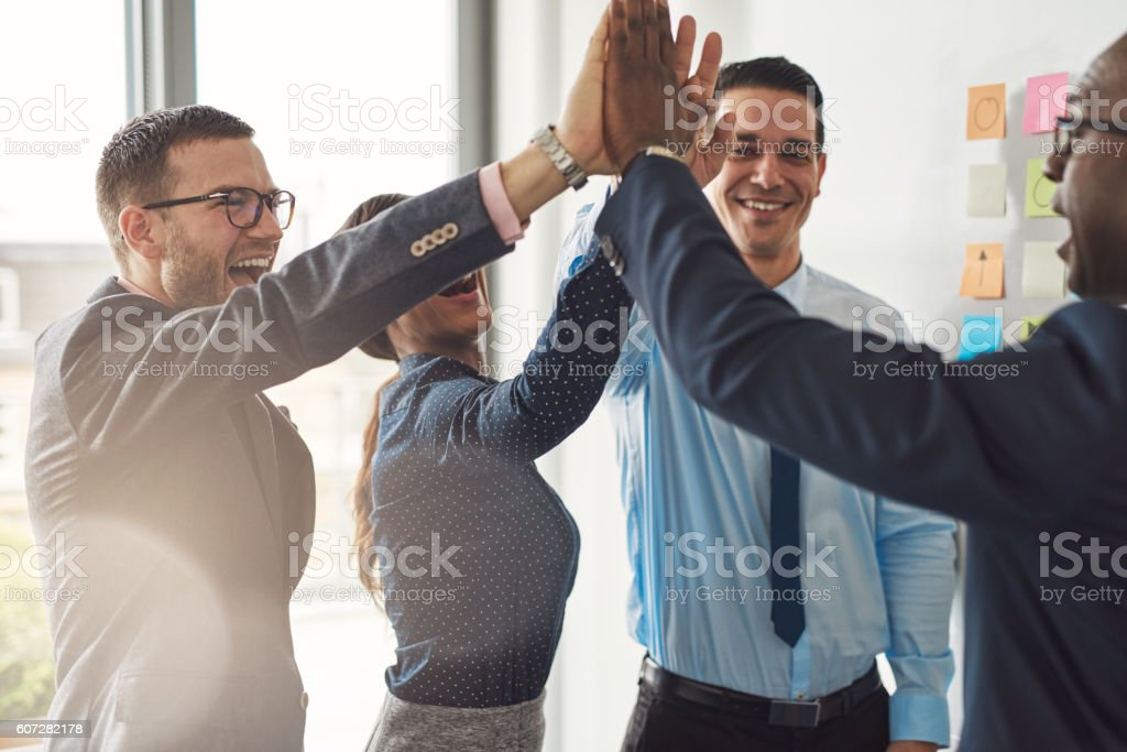 Happy successful multiracial business team Happy successful multiracial business team giving a high fives gesture as they laugh and cheer their success Adult Stock Photo