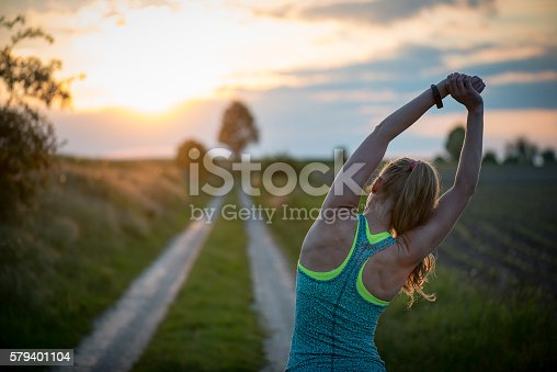 istock Happy successful sportswoman raising arms to the sky 579401104