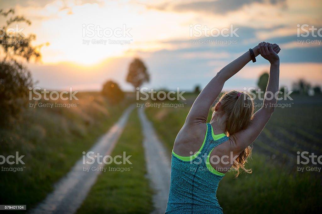 Happy successful sportswoman raising arms to the sky stock photo