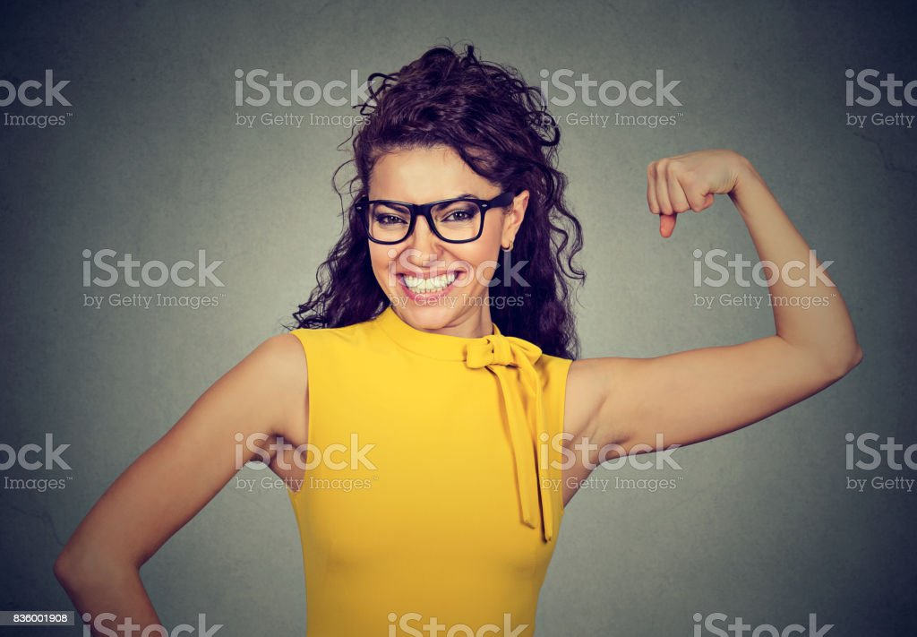Happy successful strong young woman flexing her biceps stock photo