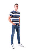 istock Happy successful young adult man with hands in jeans pockets smiling and looking at camera 1065866152