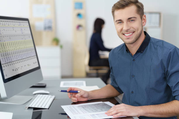 Happy successful young businessman at his desk stock photo